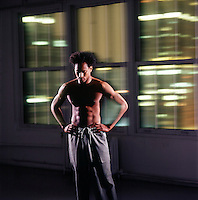 Shirtless African American man standing with blurred nighttime city windows as background