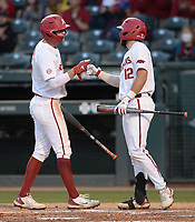 Arkansas first baseman Brady Slavens (left) is congratulated at the plate Tuesday, April 6, 2021, by catcher Casey Opitz after scoring on a double by center fielder Christian Franklin during the third inning of play against UALR at Baum-Walker Stadium in Fayetteville. Visit nwaonline.com/210407Daily/ for today's photo gallery. <br /> (NWA Democrat-Gazette/Andy Shupe)