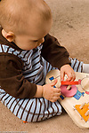 13 month old toddler boy sitting putting pieces on peg puzzle toy