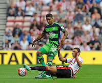 Jack Rodwell of Sunderland flies in with a challenge on Kyle Naughton of Swansea City during the Barclays Premier League match between Sunderland and Swansea City played at Stadium of Light, Sunderland