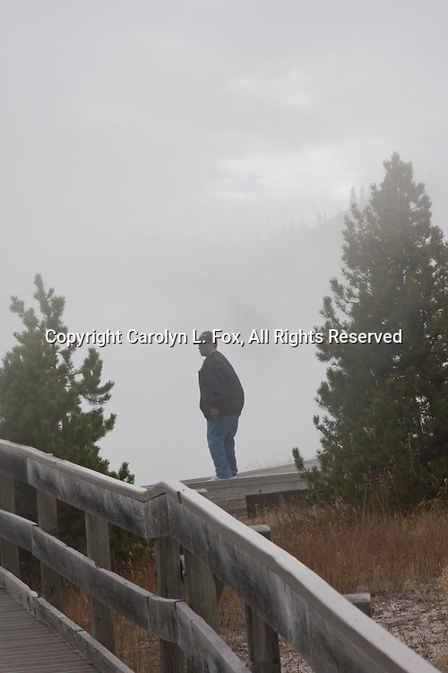 A man stands on the walkway at a geyser basin in yellowstone national park.