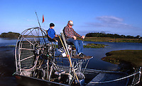Grandfather taking grandson out for a ride on an airboat in the Stick Marsh in Florida. Model released.
