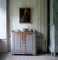 A portrait of King Gustav III hangs on the linen canvas panelled wall of the living room