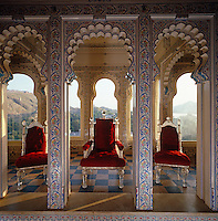 Three Bohemian crystal chairs upholstered in red velvet stand on display in this alcove punctuated with hand-painted colonnades