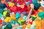 Huge piles of colourful fabrics being sorted through by Joy Saha