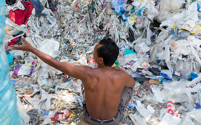 20 May 2019, Bangun Village,East Java, Indonesia: Sucipto (55) a rag picker looks at Australian branded waste in dumps at Bangun Village outside Surabaya, Indonesia. Millions of tonnes of recyclable plastic trash from Australia and Europe is dumped for rag pickers to separate and sort. The plastics are used to fuel fires at local tofu factories among other industries. Australia is illegally sending non recyclable trash hidden within this lode and the Indonesian Government is cracking down on the practice and preparing to refuse to take Australia's rubbish that is creating environmental and health issues locally. Picture by Graham Crouch/The Australian