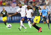 DALLAS, TX - JULY 25: Kellyn Acosta #23 of the United States and Cory Burke #9 of Jamaica chase after a loose ball during a game between Jamaica and USMNT at AT&T Stadium on July 25, 2021 in Dallas, Texas.