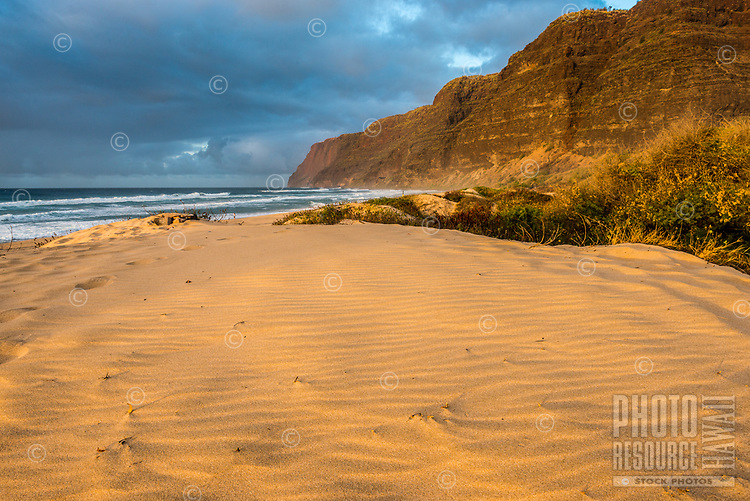 Golden sunset light falls on rippled sand at Polihale State Park on the western edge of Kaua'i.