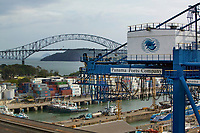 aerial photograph of the Panama Ports Company crane, tug, boats and container storagte, Port of Balboa, at the entrance to the Panama Canal, Panama; the Bridge of the Americas is in the background | fotografía aérea de la grúa, remolcador, barcos y almacén de contenedores de la Panama Ports Company, Puerto de Balboa, a la entrada del Canal de Panamá, Panamá; el Puente de las Américas está al fondo