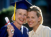 Mature college graduate woman is embraced by her proud daughter.