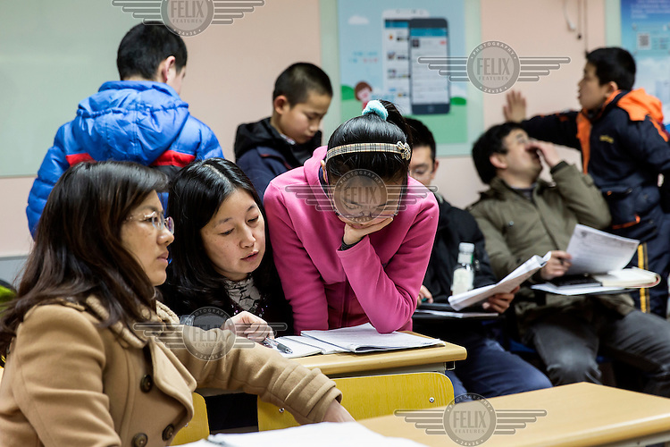 Fifth grade students and their parents look over questionnaires during one of two ten minute recess periods amid a three hour long Saturday Mathematics Olympiad class at the Xueersi cram school. With their future success pinned on their academic performance at a very early age, Chinese students and their parents are under pressure to improve their academic performance in every perceivable way.