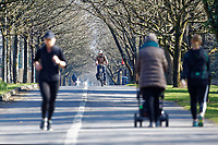 Pictured: People walk, jog and cycle on the seaside path in Swansea, Wales, UK. Friday 27 March 2020<br /> Re: Covid-19 Coronavirus pandemic, UK.