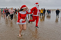 Pictured: People in festive fancy dress costumes run to the freezing cold see. Tuesday 25 December 2018<br /> Re: Hundreds of people take part in this year's Porthcawl Christmas Swim in south Wales, UK.
