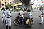 Kolkata police stops a motorbike rider to find out the reason for moving out of house during 21 days lock down in the country due to covid 19 pandemic. If commuters can not prove a suitable reason they are either sent back to home or being arrested for violating  lock down laws. Kolkata, West Bengal, India. Arindam Mukherjee.
