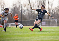 LOUISVILLE, KY - MARCH 13: Grace Bahr #32 of Racing Louisville FC kicks the ball past Abby Rodriguez #23 of West Virginia University during a game between West Virginia University and Racing Louisville FC at Thurman Hutchins Park on March 13, 2021 in Louisville, Kentucky.