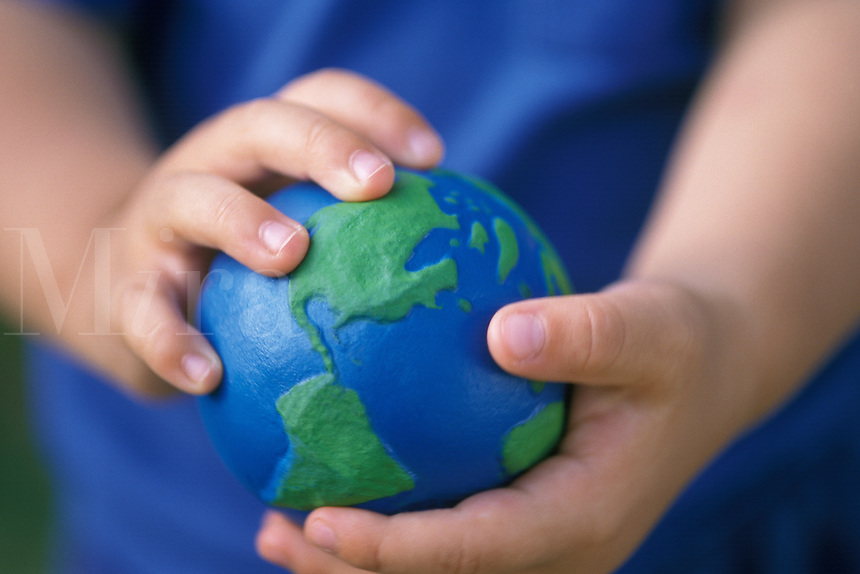 Child holding a globe in his hand.