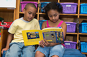 MR / Schenectady, NY. Zoller Elementary School (urban public school). Kindergarten classroom.  Two bilingual students, both who are native Spanish speakers, read Spanish-language book in classroom. Book is entitled Las formas donda jugamos (Shapes Where We Play) by Ellen Senisi. Left: boy, 6, African American /  Puerto-Rican American; Right: girl, 6, Hispanic American. MR: Car38, Fue3. ID: AM-gKw. © Ellen B. Senisi.