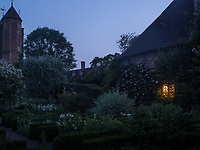 As evening falls, a single light from a window illuminates the 'white garden' at Sissinghurst Castle
