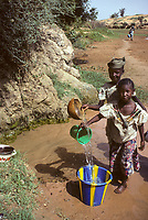 Niger, near Niamey.  Girls Filling Water Buckets with Water from a Spring.