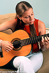 17 year old teenage girl playing musical instrument guitar vertical caucasian