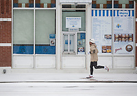 A runner passes the front of the Walmart Museum, Sunday February 14, 2021, on the Bentonville Square. (NWA Democrat-Gazette/Spencer Tirey)