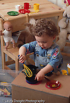 2 year old toddler boy pretend play cooking in toy kitchen vertical