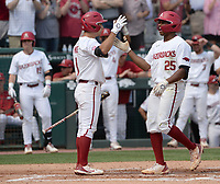 Arkansas center fielder Christian Franklin (25) is congratulated at the plate Friday, June 4, 2021, by second baseman Robert Moore after hitting a solo home run during the fourth inning of the Razorbacks' 13-8 win over New Jersey Institute of Technology in the first game of the NCAA Fayetteville Regional at Baum-Walker Stadium in Fayetteville. Visit nwaonline.com/210605Daily/ for today's photo gallery.<br /> (NWA Democrat-Gazette/Andy Shupe)