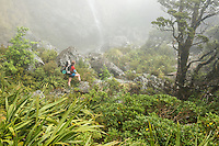 Woman tramper under Earland Falls on Routeburn Track, Fiordland National Park, Southland, South Island, UNESCO World Heritage Area, New Zealand, NZ