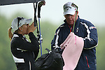 """American Morgan Pressel (left) tries to stay dry while her caddie, Barry Cesarz """"Rock"""" cleans the iron club on the golf range before Round 1at the LPGA Championship at Locust Hill Country Club in Pittsford, NY on June 6, 2013"""