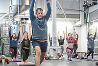 Attendees perform a yoga movement, Saturday, February 13, 2021 at the Bentonville Brewing Company in Bentonville. The brewhaus hosted a free yoga class inside the brewery due to the cold weather. Check out nwaonline.com/210213Daily/ for today's photo gallery. <br /> (NWA Democrat-Gazette/Charlie Kaijo)