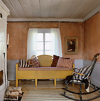A rocking chair and wooden sofa furnish this small sitting room with bare plaster walls
