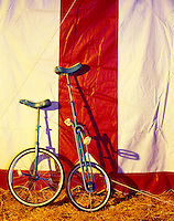 Circus unicycles resting against the big top tent.