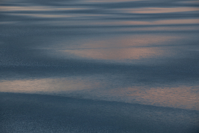 An abstract look at the sunset reflecting off the ice on Burnt Pond in New York State's Adirondacks.
