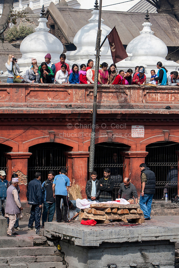 Nepal, Pashupatinath.  Cremation Stages.  Family Members Watch while others  Prepare to Place  the Corpse on the Cremation Site.