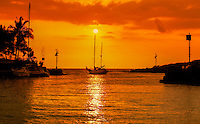 A sailboat heads towards the sunset from Honokohau Boat Harbor near Kailua-Kona on the Big Island of Hawai'i.