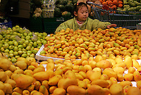 A young girl picks fruit at a Carrefour Supermarket in Shanghai, China. According to a recent report, China has surpassed the United States in total consumption of every basic food, energy, and industrial commodity except oil, as well as goods such as television sets, refrigerators and mobile phones. However the per capita income for China is only roughly one seventh of that of the U.S..19 Feb 2005