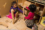 Preschool 4 year olds two girl in block area one holding onto another block being used by the other and looking inquiringly, negotiating