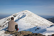 A hiker takes in the view of Mount Lafayette from along the Appalachian Trail (Franconia Ridge Trail), on the summit of Mount Lincoln, in the White Mountains of New Hampshire during the winter months.