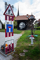 Switzerland. Canton Fribourg. Neyruz. Traffic sign of work in progress and dead end. Fire Hydrant and a metal sculpture by local artist. A large portrait of the artist Jean Tinguely, who is buried in the village, is painted on a tarpaulin and hanged on a barn. Jean Tinguely (22 May 1925 – 30 August 1991) was a Swiss sculptor. He is best known for his sculptural machines or kinetic art, in the Dada tradition; known officially as metamechanics. Tinguely's art satirized the mindless overproduction of material goods in advanced industrial society. 21.05.2019 © 2019 Didier Ruef