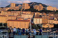 People watching the sunrise over Ajaccio from the deck of a docked ferry, Ajaccio, Corsica, France.