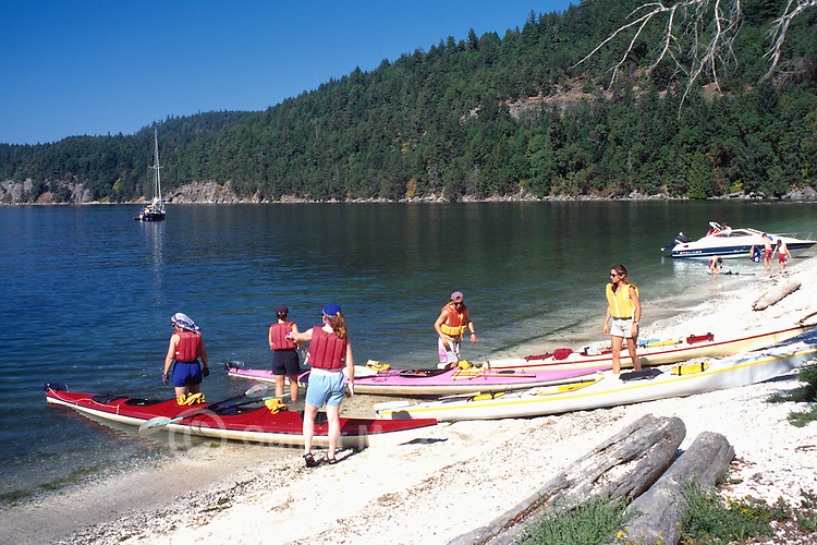 Galiano Island, Southern Gulf Islands, BC, British Columbia, Canada - Kayakers preparing for Ocean Kayak Trip at Montague Harbour Provincial Marine Park, Summer