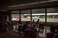 Switzerland. Canton Ticino. Zurich Airport  Swiss airplanes on the airport tarmac. Passengers seated in waiting room. Swiss International Air Lines AG (stylised as SWISS), commonly referred to as Swiss, is the national airline of Switzerland. Zurich Airport (German: Flughafen Zürich, IATA: ZRH, ICAO: LSZH), also known as Kloten Airport, is the largest international airport of Switzerland. 29.05.2019  © 2019 Didier Ruef