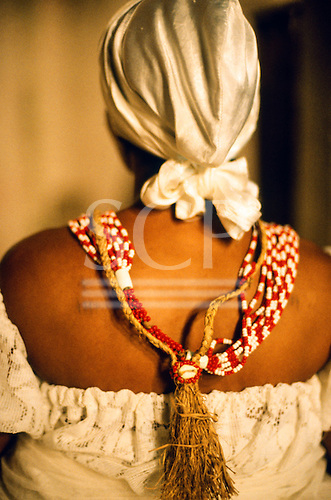 Recife, Brazil. Follower of Candomble from the back; white turban and red and white beads with buzios cowrie shells.
