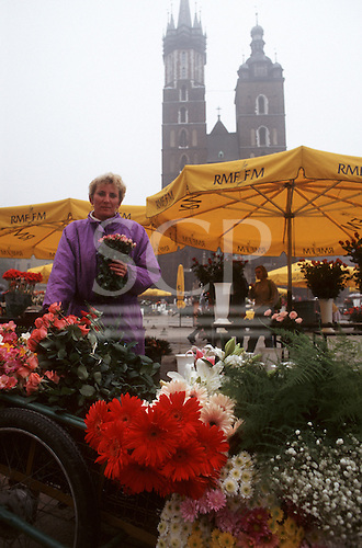 Kracow, Poland. Flower stall with yellow sunshades on the Old Town square.