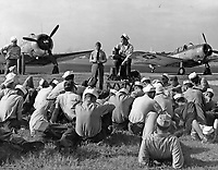 Students receiving familiarization with flight photography at Chevalier Field.  Instructor with camera on platform is J. L. Estano PhoM 1/c, and CPhoM, D.D. Kendal to the left.  SBD in background.