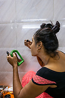 India, Maharashtra, Mumbai, Bombay, red light district. The sex workers in Simplex brothel apply make up while getting ready for an evening of work.