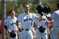 Dartmouth Big Green catcher Kyle Holbrook (9) bumps helmets with Michael Calamari (right) after scoring a run during a game against the Villanova Wildcats on March 3, 2018 at North Charlotte Regional Park in Port Charlotte, Florida.  Dartmouth defeated Villanova 12-7.  (Mike Janes/Four Seam Images)
