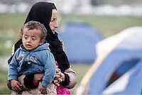 Pictured: A migrant woman with her young child Monday 07 March 2016<br /> Re: Refugees at the Greek FYRO Macedonian border in Idomeni, Greece.
