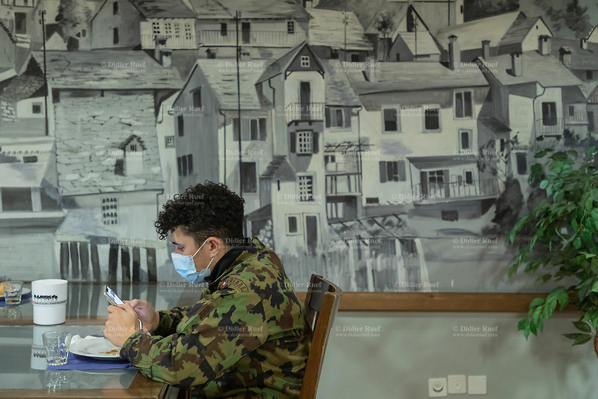 """Switzerland. Canton Ticino. Losone. Hotel Garni Tiziana. A soldier dressed with his camouflage uniform seats alone at the breakfast room. He checks social network on his mobile phone. He wears a mask to protect himself from the coronavirus (also called Covid-19). Due to the spread of the coronavirus (also called Covid-19), the Federal Council has categorised the situation in the country as """"extraordinary"""". The army was called upon to provide its troops in terms of medical assistance. The militia soldiers from medical troops were called by the Swiss army for the first time since World War II. Under the country's militia system, professional soldiers constitute a small part of the military and the rest are conscripts or volunteers aged 19 to 34 (in some cases up to 50). He will be on duty the all day at the Ospedale Regionale di Locarno La Carità. 20.11.2020 © 2020 Didier Ruef"""