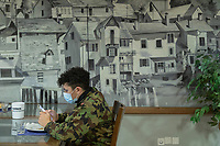"Switzerland. Canton Ticino. Losone. Hotel Garni Tiziana. A soldier dressed with his camouflage uniform seats alone at the breakfast room. He checks social network on his mobile phone. He wears a mask to protect himself from the coronavirus (also called Covid-19). Due to the spread of the coronavirus (also called Covid-19), the Federal Council has categorised the situation in the country as ""extraordinary"". The army was called upon to provide its troops in terms of medical assistance. The militia soldiers from medical troops were called by the Swiss army for the first time since World War II. Under the country's militia system, professional soldiers constitute a small part of the military and the rest are conscripts or volunteers aged 19 to 34 (in some cases up to 50). He will be on duty the all day at the Ospedale Regionale di Locarno La Carità. 20.11.2020 © 2020 Didier Ruef"